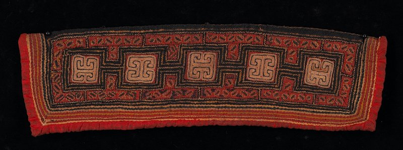 red; primary design has five geometric shapes connected to each other in black and tan; bordered with small strips of embroidered appliques; brown lining