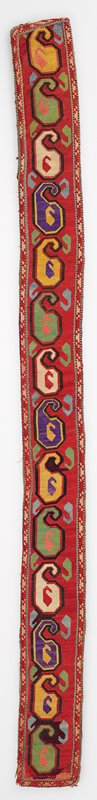 Warp-twined band. Pieced ikat lining. Overall silk cross stitch embroidery on a cotton ground. An applied woven band finishes the four edges. There is a backing of pieced silk/cotton ikat. Red background with yellow, green, purple, tan.