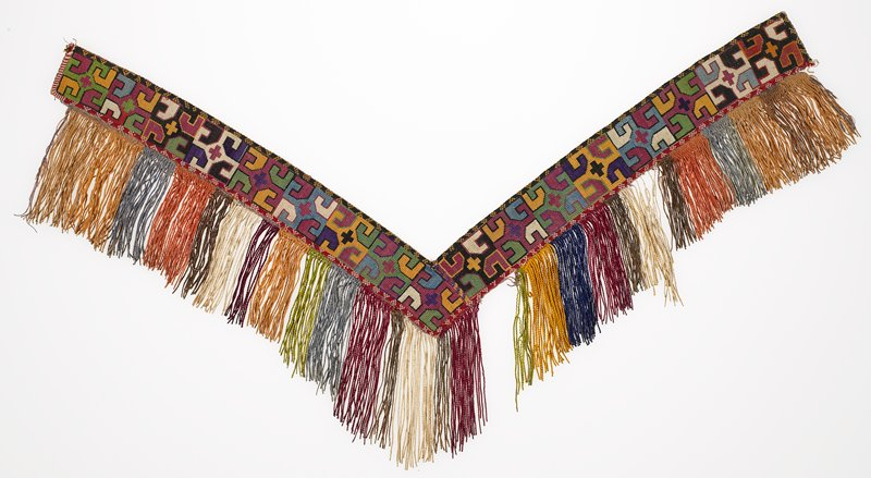 Warp-twined (LM) edge, Pieced fringe with warp-twined and plain-weave heading. Pieced, printed lining Overall silk cross stitch embroidery on a cotton ground. There is an integral cross stitched edging, a silk and cotton multi-colored fringe, and a red printed cotton backing.
