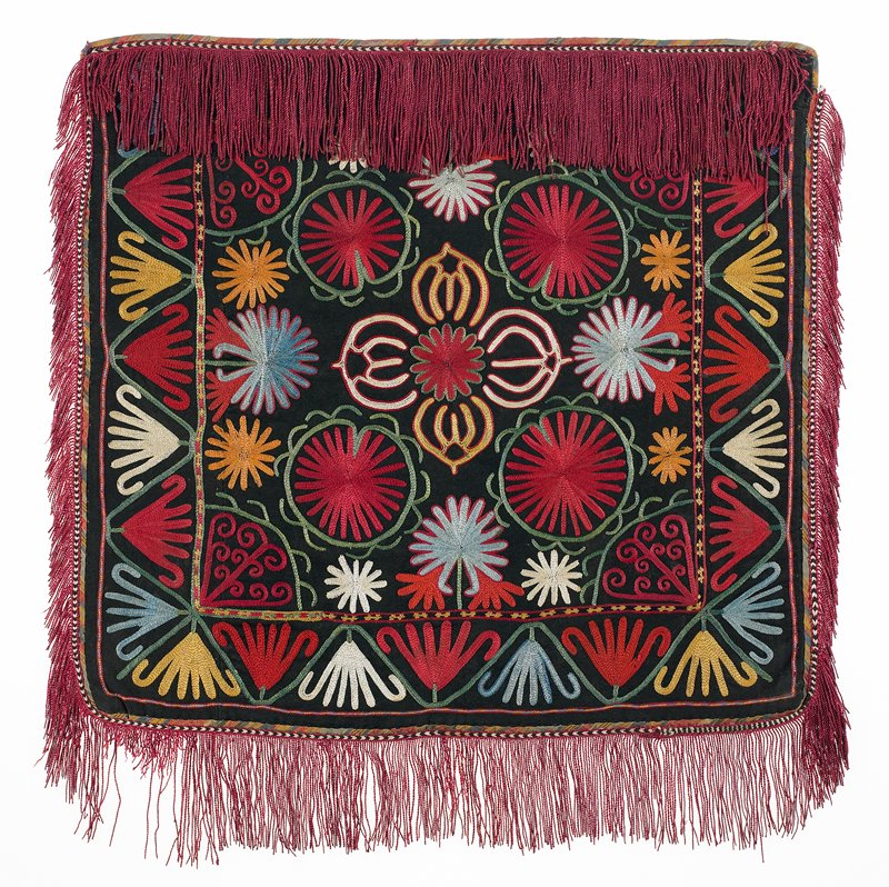 Pieced fringe with warp-twined (tablet) heading and cloth band Pieced, block-printed lining. Pieced, black wool ground with polychrome silk embroidery. Striped cotton twill binding; embroidered silk tape edging with integral fringe. Red dominates. Center square with wide embroidered border on 3 sides. The embroidery is presently hand stitched to a fabric covered mount; the verso is not visible. Mounted and stitched through a white scrim and screen to a white linen covered strainer (wood).