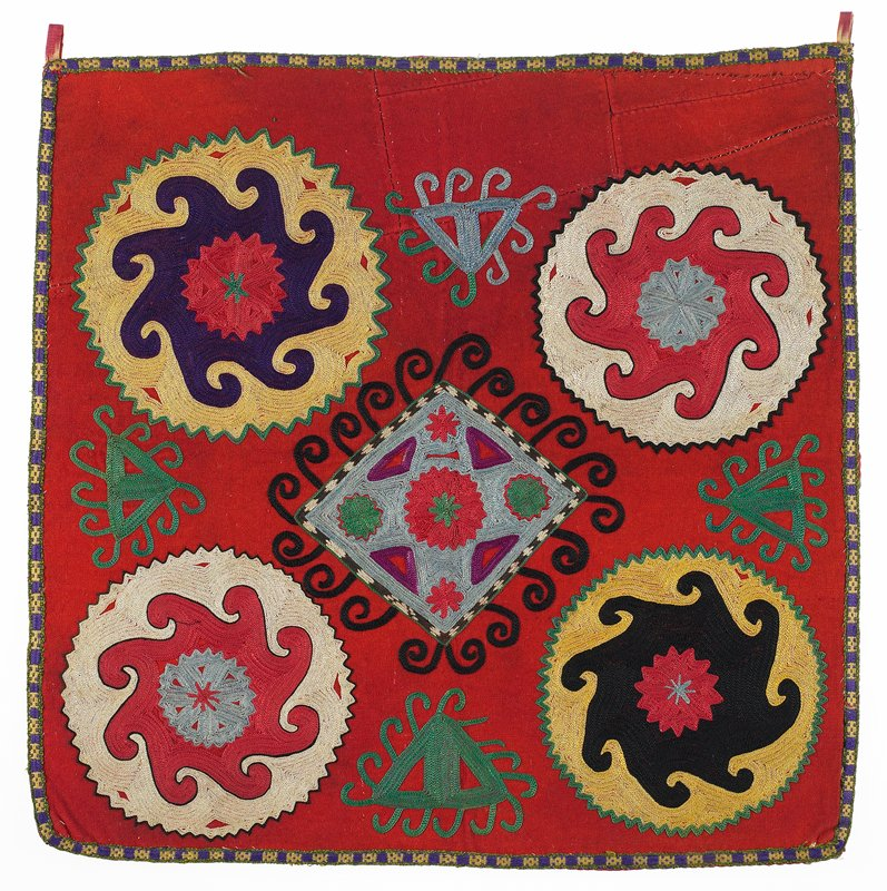 Handwoven band, Printed lining. Red wool ground, pieced in the upper six inches. Polychrome silk and synthetic embroidery. There is a woven cotton edging strip on the four sides. The hanging tabs are silk/cotton ikat. The cotton backing is printed with 'moderne' angular gray shapes on a red ground. Chain stitch separated with back stitch dominate fill.