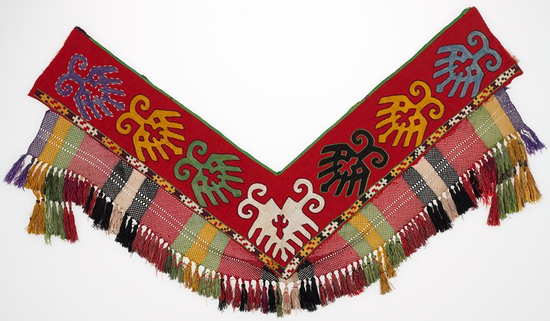 Braided-net fringe, cloth band, Pieced plaid lining. Red cotton flannel ground with polychrome silk embroidery. There is a wide braided band at left and lower edge, with silk and metallic wrapped tassels. A green silk binding finishes the upper edge. There is a woven plaid cotton packing, secured to the reverse with starch paste. Made to lie flat at corner with fringe hanging over edge.