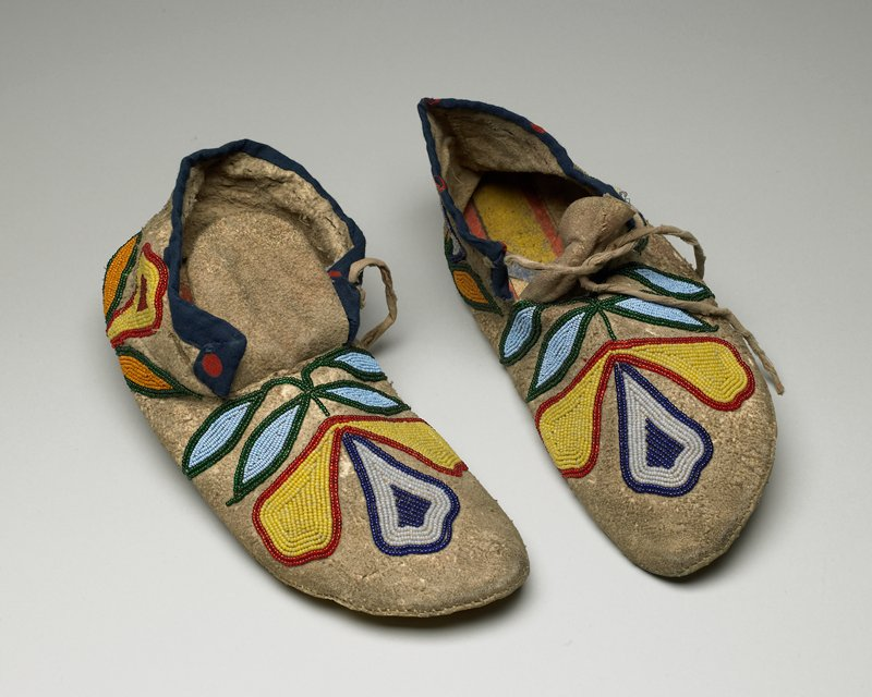 rawhide soles with pigment decorations at interior (may be reused parfleche fragments?); floriform beaded designs overall; blue cloth collar trim with red dots