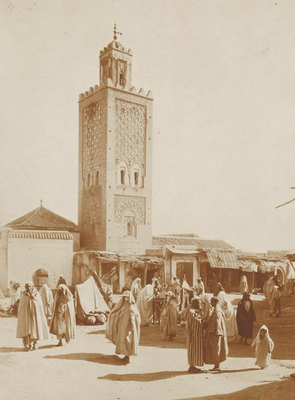 square tower, with minaret at top; figures wearing robes in foreground; view of Morocco