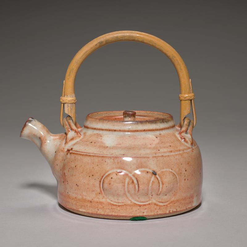 orange-red glaze with white undertones; large, flat foot; wide body with three bulging circles on each side; bamboo handle