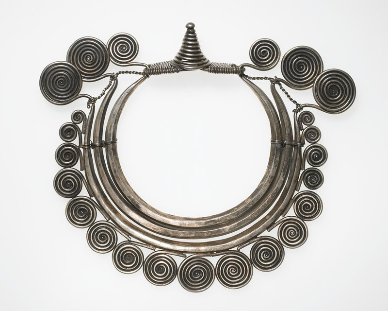 collar style, with three beveled metal neckbands terminating in large graduated spirals; seventeen graduated spirals around bottom band; spiral cone closure
