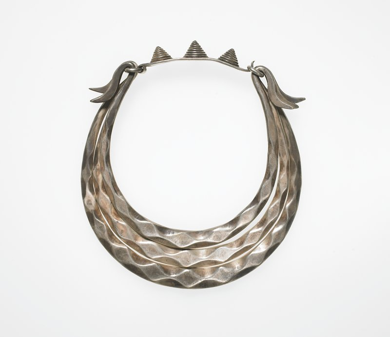 collar-style; three heavy silver bands with wavelike designs, graduated; hooks at ends; three spiral cones on closure