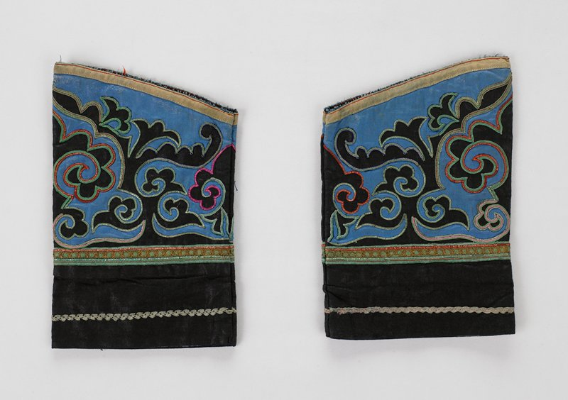 blue lined sleeve extensions with black edge and scroll work cut-out design on blue background with silver metal outlining; green horizontal tape with gold and silver metal trim in interlocking circle pattern