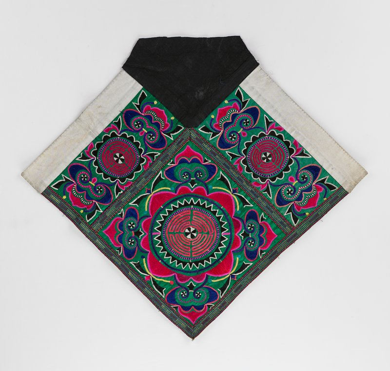 square with center point down and top has black insert; multi-colored running stitch embroidery on green background with large circle in center panel; side panels are rectangular pattern with similar embroidery; applied linear border in multi-colors; paper backing; two sides have wide white border