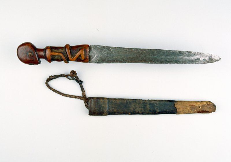 metal blade, carved wooden handle with squatting female figure, leather sheath, tooled with vertical zig-zags on one side, looped leather strap on other side, plain leather tip with traces of animal hair on one side