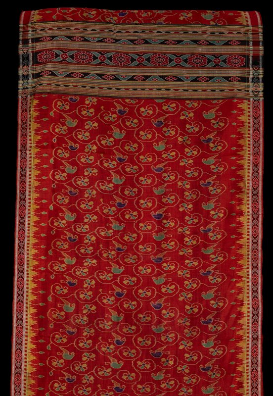 weft and warp ikat; red/orange sari with floral and bird patterning throughout center in green, purple and yellow; warp ikat pattern along length edges; stripes and weft ikat across one end