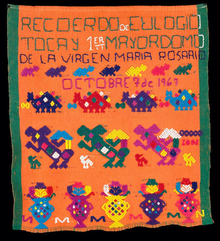 "orange cotton ceremonial ""banner""; inscription reads, ""Recoerdo de Eulogio Tocay 1er Mayordomo de la Virgen Mario Rosario Octobre 7 de 1967""; four rows of multicolor facsimile of fauna and flora; green selvedge on sides"