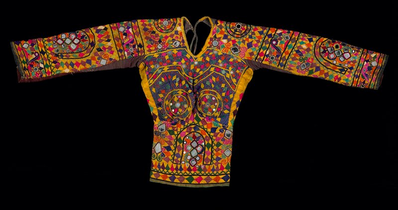 yellow dominates multicolored embroidery; satin stitch, chain stitch, outlined mirrors--large and small; long sleeves; waist ties; yellow fabric, green lining; diamond shapes dominate embroidery; V-neck; neck ties; also print lining at back edges; body shape