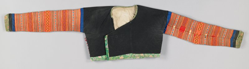 black cotton; side front opening with 11 rolled red loops and green plastic buttons on commercial green print piping; sleeves have narrow applique rows alternating with commercial and hand embroidery in orange, red and blue; lined with tan cotton