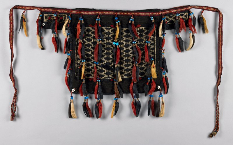 cotton label 198; woven bags; stripped patern on back; front--black and white woven pattern; hand sewn in blanket stitch; front top edge has narrow woven ties ending in braids; two small side bags attached at top; many beaded fringed tassels and some shells at lower edge; colors of tassels are red, black and white