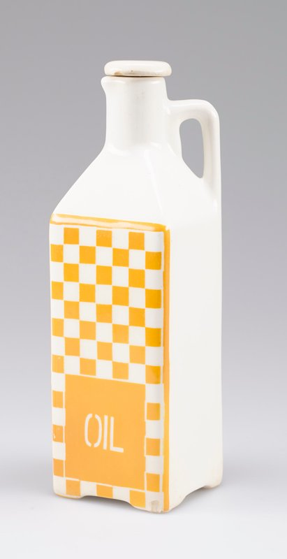"square body; short round neck and small spout; squared-off handle; white porcelain with one side decorated with yellow-orange checkerboard and ""OIL"" in white; small stopper"