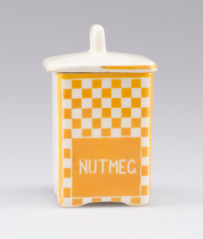 "small square container with cover with small handle; white porcelain decorated with yellow-orange checkerboard and ""NUTMEG"" in white on front; stripe around edge of cover on front and sides"