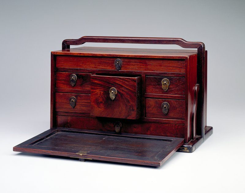 Box with handle at top and along sides; resting on low base; 7 inner drawers behind a removable front door with square metal closure