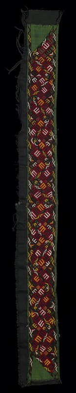 red with white, black and yellow zigzag geometrics embroidered in chain stitch through green silk cloth and coarse, weft faced black cotton; one long edge overcast; tacked to black fabric along other long end, selvedge edges and both ends of embroidery; green silk fabric seamed in 2 pieces; black cotton fabric has a center seam