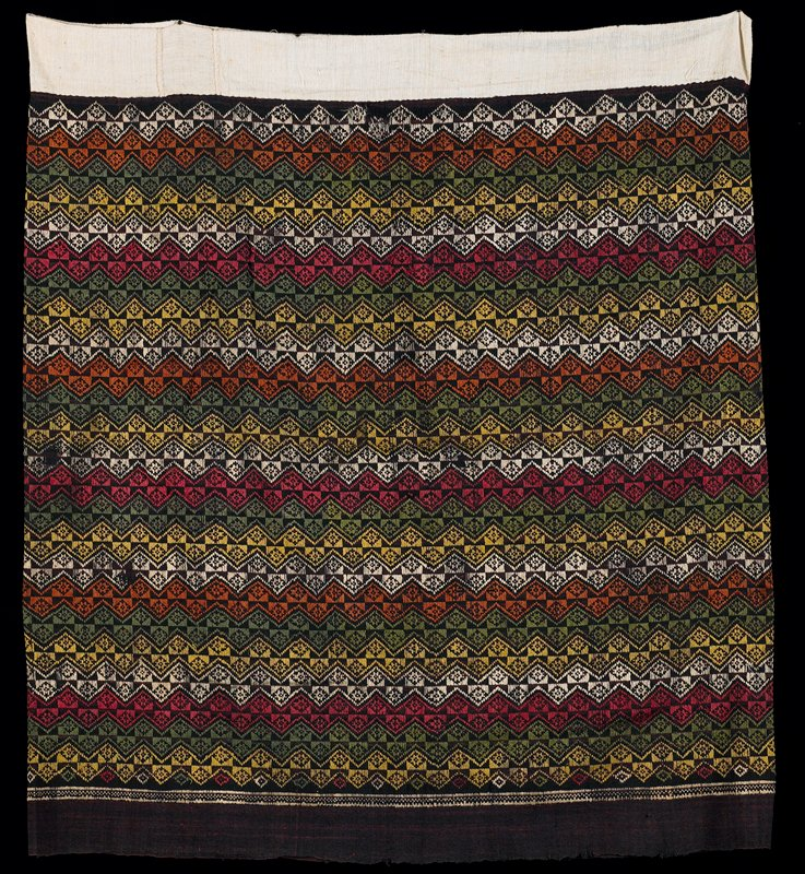 """brown cotton woven in approximate 1"""" horizontal zigzag pattern in brown, green, red, yellow and white; 2 1/2"""" off-white hem is hand sewn; brown border is unfinished; hand stitched together"""