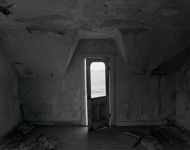 old room with gabled ceiling; cracked and peeling walls and ceiling, with debris on floor at right and left; door at center slightly ajar, with a view of a farm field through window in door