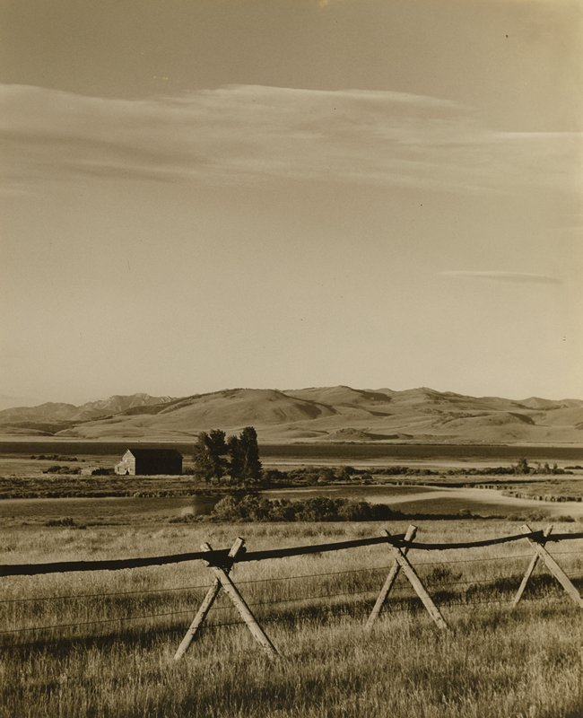 farmland, pond and mountains in background; fence in foreground; barn at L in middle ground; expansive sky