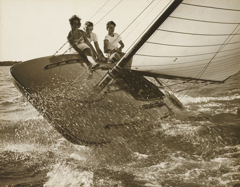 two young men wearing t-shirts and a young woman wearing a halter top riding on the side of a sailing boat