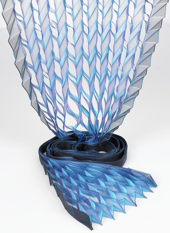 long sash in shades of blue and purple; folded and pressed into triangular patterns; blue thread loops at points on one end