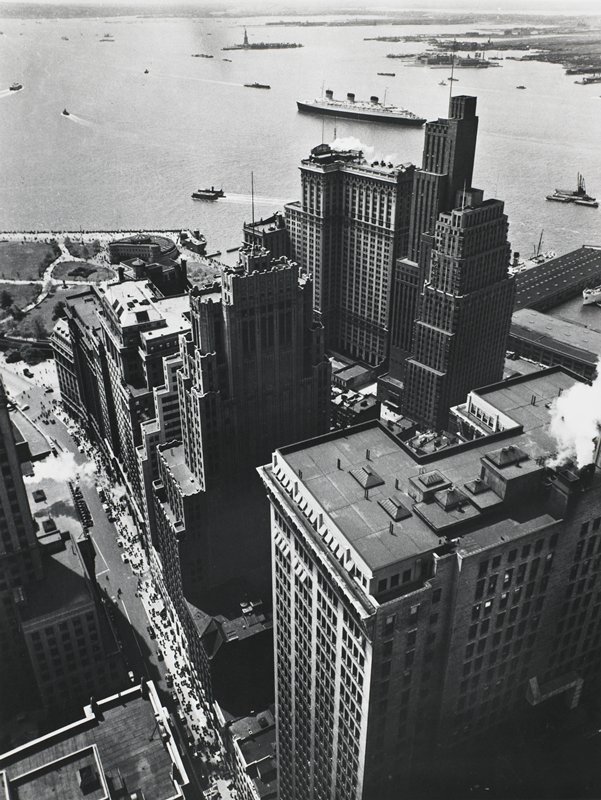 bird's eye view of skyscrapers in New York; water, ships, Staten Island and Statue of Liberty visible at top