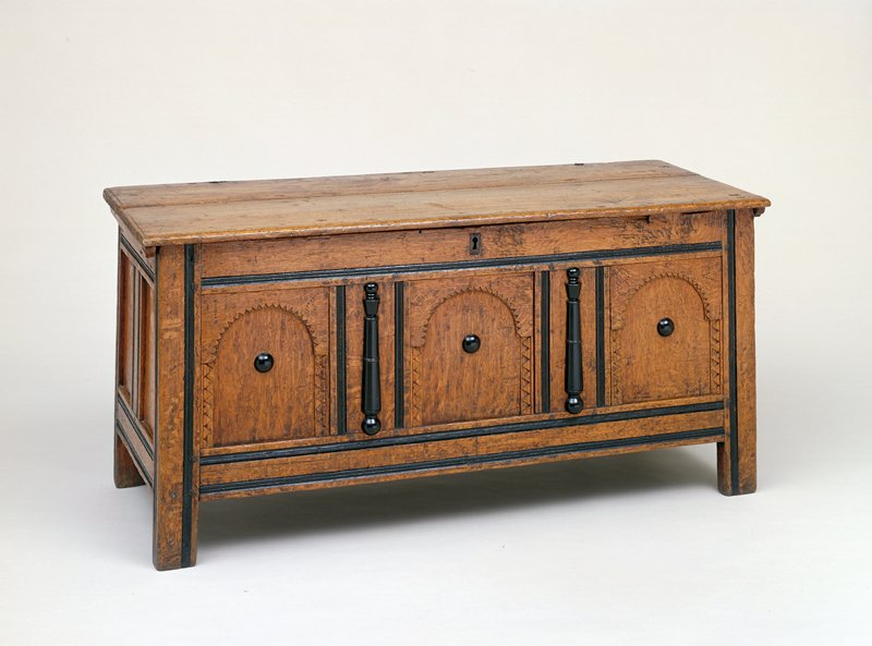 chest, New England oak and pine panelled; of a type popularly known as 'Connecticut Chests' and believed to have originated in that locality; constructed of quartered oak, the hinged lid of pine; the front is divided into three arched panels carved with serrated ornament and framed by ebonized split balusters and round bosses; ends are similarly panelled; stands on extensions of the corner stiles