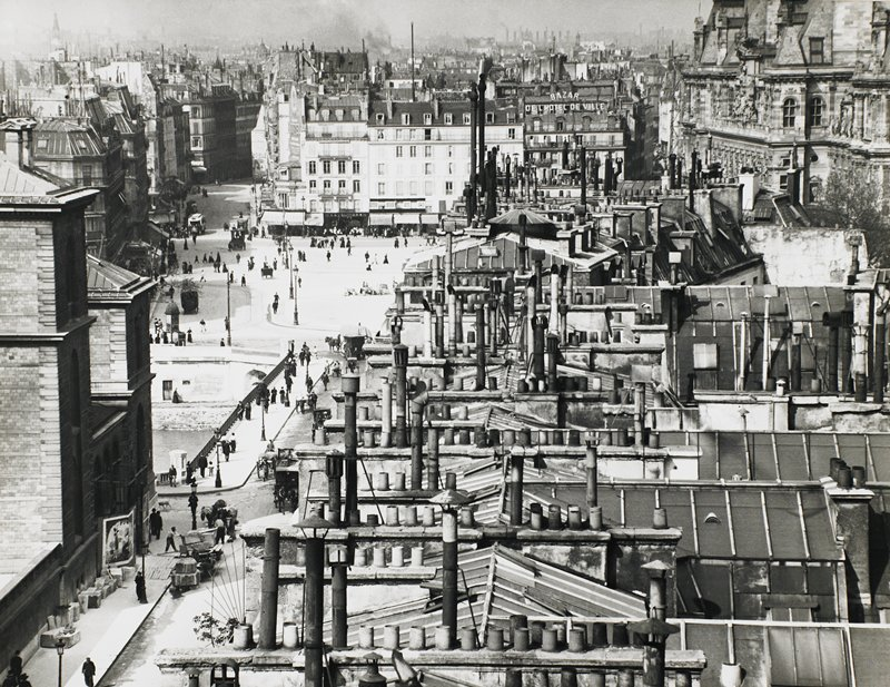 bird's eye view of city rooftops with many smokestacks and chimneys; people and horse-drawn carriages in streets and plaza in middle ground