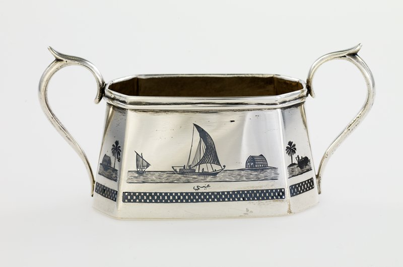 tapered octagonal body with wide mouth opening; two handles; body decorated with sailboats, buildings, camels, palm trees and figures