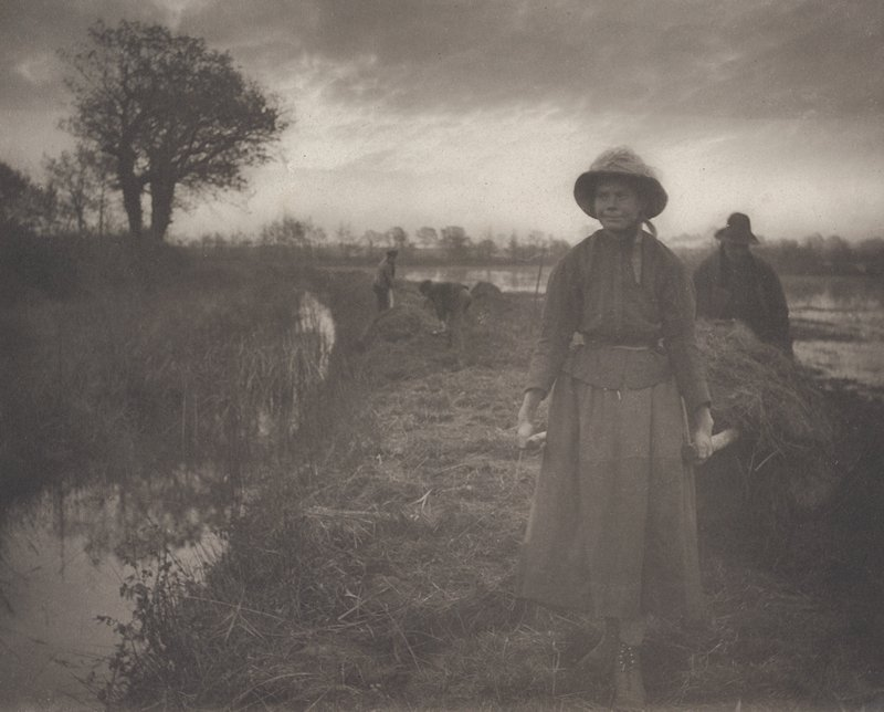 woman wearing a hat and ankle-length skirt, pulling a barrow of hay; man behind barrow; two other figures in middle ground, center