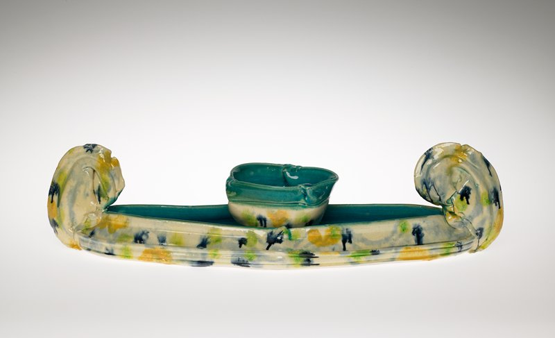 boat-shaped tray with looped forms at ends; small bowl with three pinched folds at top rim; exterior of each piece is white with green dark blue and yellow blotches; interiors are turquoise blue