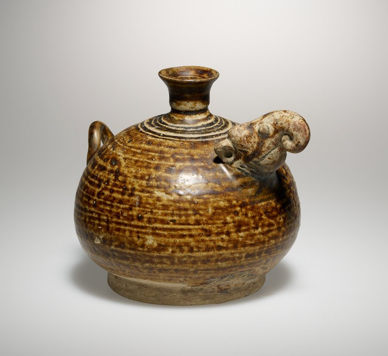 rounded vessel on wide ring foot; small, outward-flaring spout; small elephant's head with trunk curled under extending from shoulder; long curled tail at shoulder opposite head; brown glaze