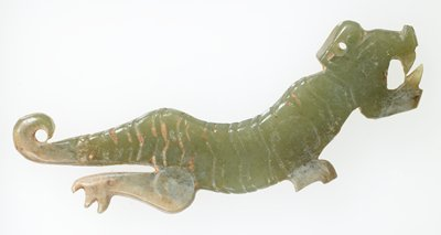 stylized tiger, similar to 50.46.251, further articulated; open mouthed tiger with two teeth shown; the back curves in convex form and the tail curves outward into an open worked pendant hole; incised transverse strips decorate the main body of the animal, on both sides identically; translucent green jade; traces of clay-like substance