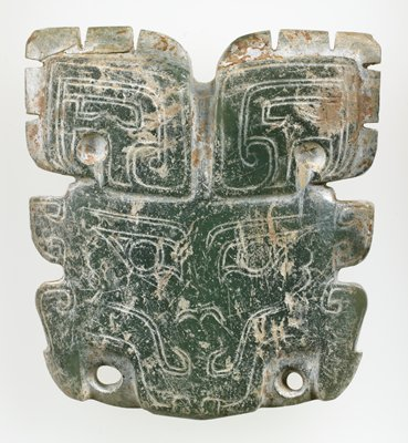 Mask of a monster like animal (t'ao-tieh); carved interrupted outline; incised double line on both sides, detailed features of the mask on the front side, one at the edge of each 'jaw' of the animal mask. Calcified green jade; traces of earth like substance on the back.