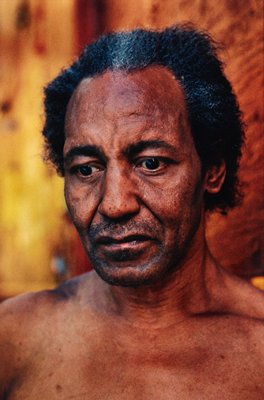 portrait of head and shoulders of dark-skinned man, looking down; matted